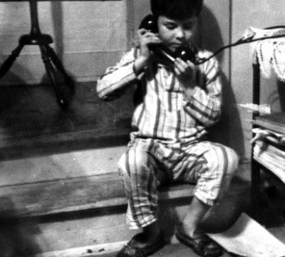 "Homer ""Sonny"" Hickam, Jr., talks to his dad on the coal mine black phone, 1948."